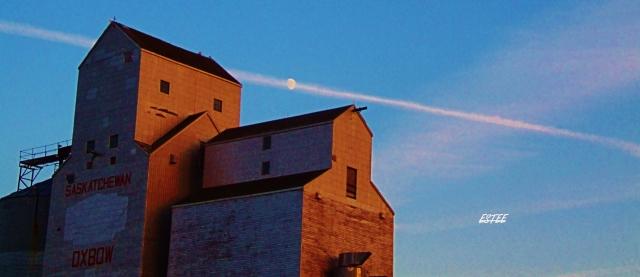 A prairie grain elevator, a chemtrail and the moon....
